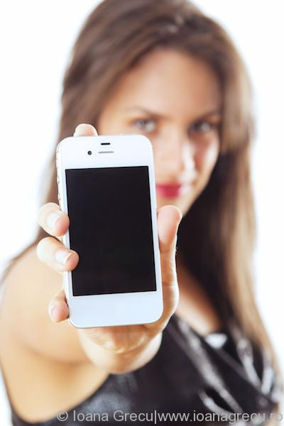 Young woman showing smartphone