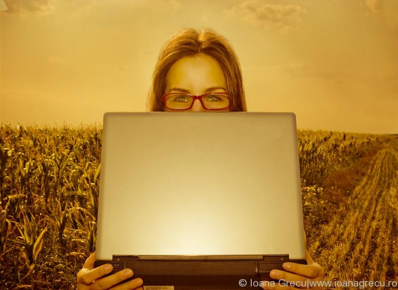 Stock photo of woman with laptop in a field